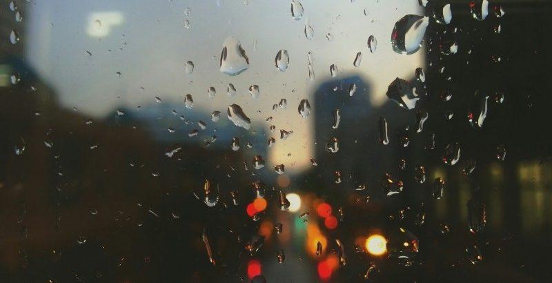 illuminated-city-behind-windshield-in-rain