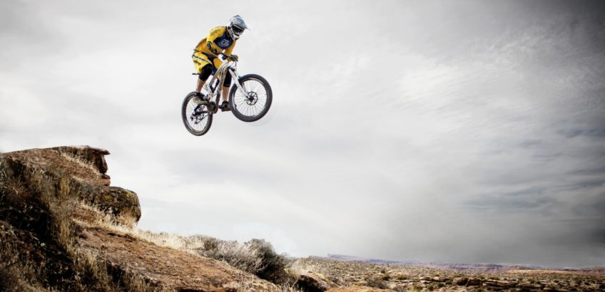 mountain-biker-jumping-over-rocks